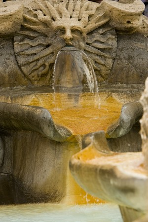 Sun face within the Barcaccia fountain in Rome, Italy
