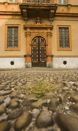 Ornate entryway on building in Milan, Italy, with soft focus cobblestone street in foreground