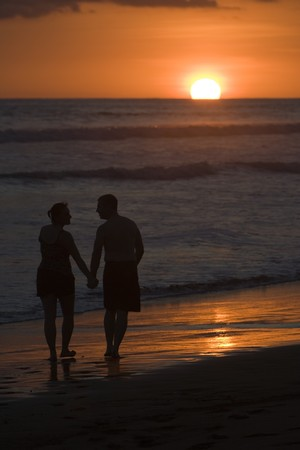 A man and woman holding hands stroll down a beach during sunset. Stock Photo