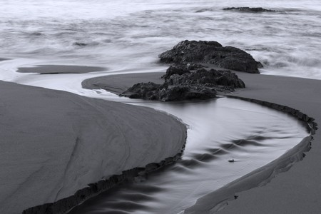 a stream of water carves an inlet to the sea through the beach sand in Black and White Stock Photo