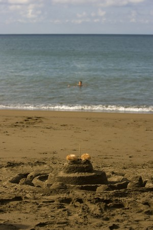 A sand castle in the forground and a soft focus person floating in the ocean in the background