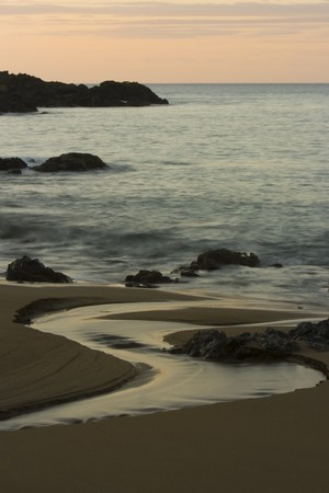 Water flows past rocks on a beach into the ocean at sunset