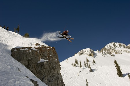 A skier jumping cross tips off cliff with mountain in background Stock Photo