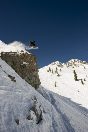 A Skier launches straight off a cliff with mountains in background Stock Photo
