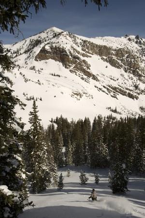A lone Powder skier under a tall mountain peak Stock Photo