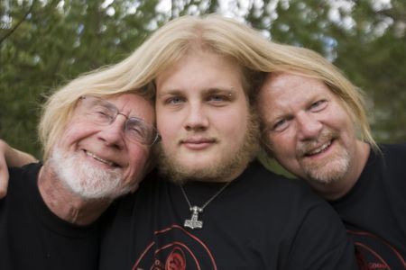 Three generations of men, two bald, one long hair, having fun together photo