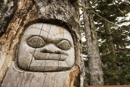 Carved totem face on a tree in the forest Stock Photo