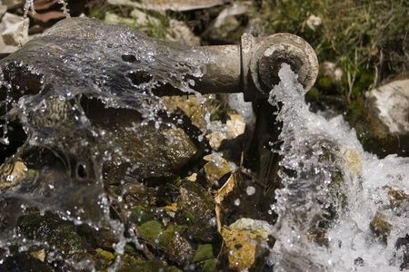 A large leaking pipe shoots water outdoors onto mossy rocks