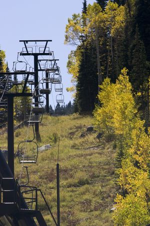 A Ski chair lift sits still next to fall colored forest