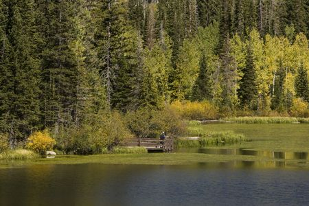 Two men talk on dock at lake surrounded by fall colored trees.