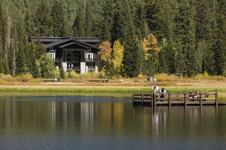 A family of four looks into Slver Lake Surrounded by Fall colored trees. Stock Photo