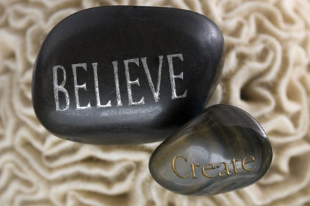 The words Believe and create, on stones with soft Brain Coral background.