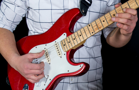 The hand of a man in a white shirt playing a red guitar.