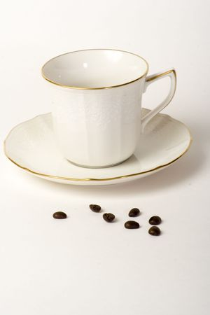 Coffe cup and saucer with a few coffee beans