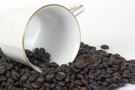 Coffee cup on its side laying in a pile of coffee beans