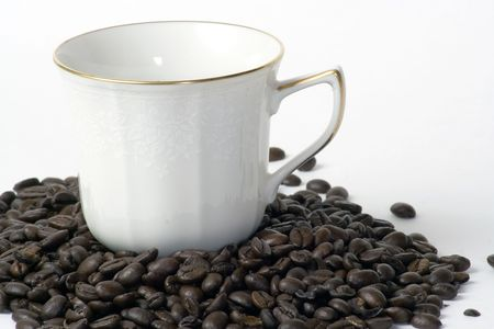 A coffee cup sitting in a pile of coffee beans Stok Fotoğraf