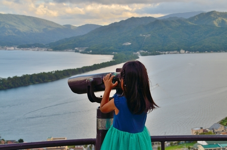 mountain peek: Girl seen through a telescope Stock Photo