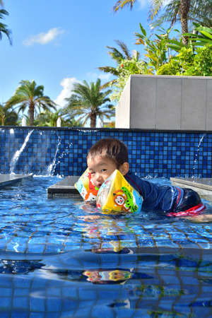 Boy playing in bright blue pool