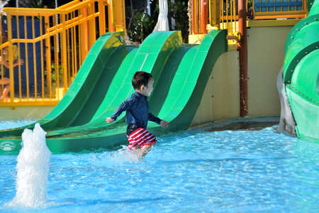 In the pool with playground equipment, a boy sucks