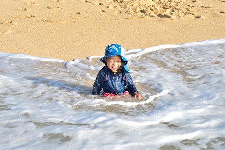 A boy playing in the waves of Okinawa 版權商用圖片