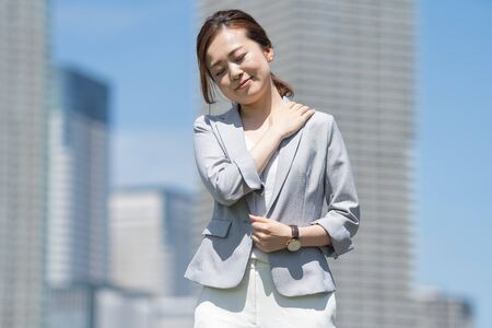 Businesswoman suffering from stiff shoulders