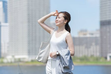 Businesswoman suffering from strong sunlight 스톡 콘텐츠