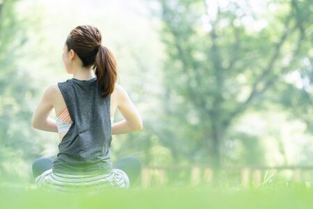 A woman doing yoga stretches in the park 写真素材