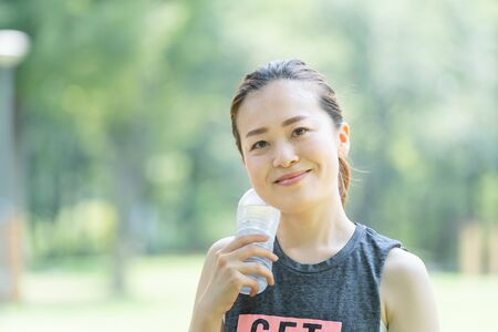 A woman who rehydrates while exercising (yoga) in the park 免版税图像