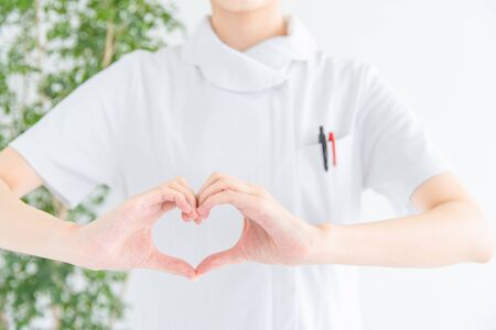 a woman in white who makes a heart with her hands