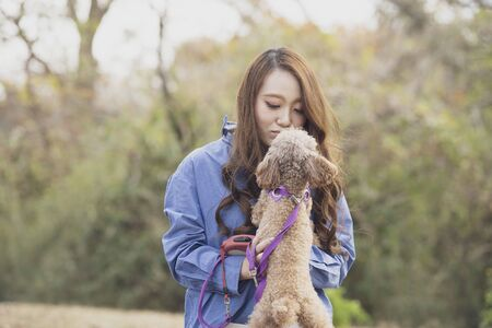 A woman walking in the park with her pet