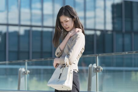 A businesswoman with a pain in her shoulder Imagens