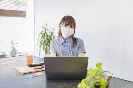 Woman wearing a mask and working remotely in the living room at home