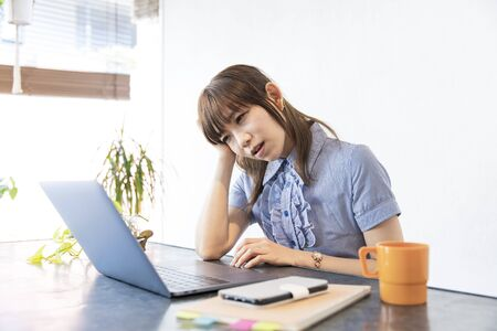Asian business woman tired of desk work by remote work Foto de archivo