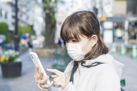 Asian woman using the call function of the smartphone with the mask on