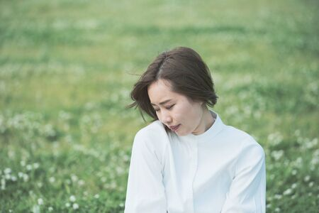 Asian young woman showing a relaxed expression on the meadow Stock Photo