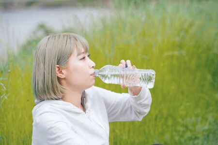 Asian young woman hydrating during exercise in urban green space Foto de archivo
