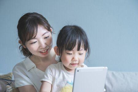 Maman et sa fille assises sur un canapé et utilisant une tablette Banque d'images