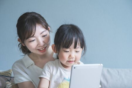 Mom and daughter sitting on a sofa and operating a tablet device Imagens