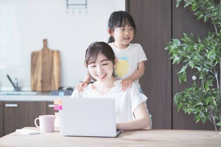 Asian woman doing telework in home room while playing with her daughter