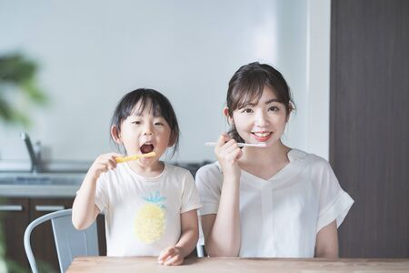 Asian young mom and daughter brushing teeth in the room