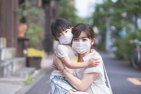 Asian mom and daughter wearing masks and going out on a sunny day