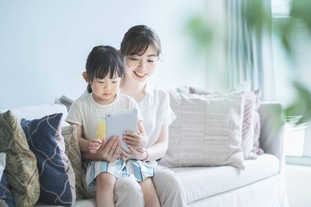Mom and daughter sitting on a sofa and operating a tablet device