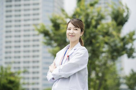 Asian female healthcare worker in white coat posing outdoors