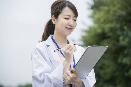 Asian female medical worker in white coat with medical chart and pen