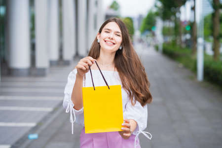 Young woman holding a paper bag with presents with a smile