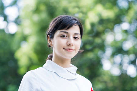 Outdoor portrait of young woman posing in white coat on fine day