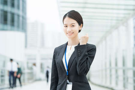 Asian young business woman in a suit posing with a smile and cheering