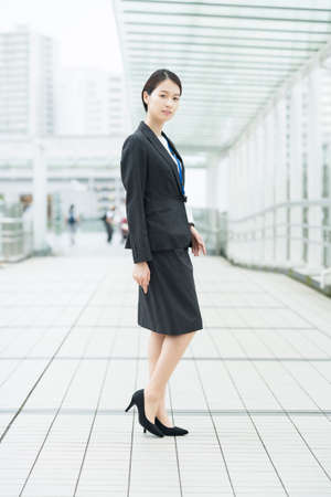 Asian young business woman in a suit posing with a smile and cheering Imagens