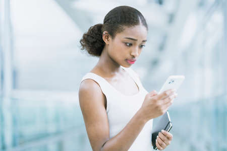Young business woman operating by looking at the screen of the smartphone