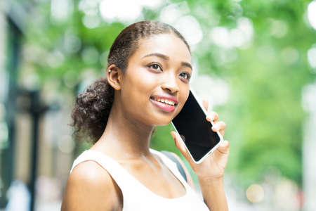 Young business woman calling by putting a smartphone on the ear